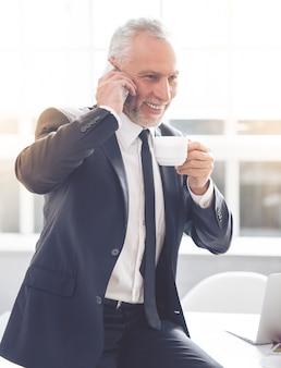 De zakenman in klassiek kostuum spreekt op mobiele telefoon.