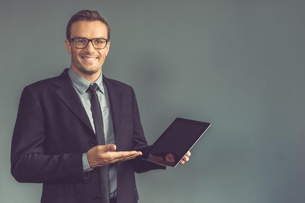 De zakenman in klassiek kostuum toont een digitale tablet