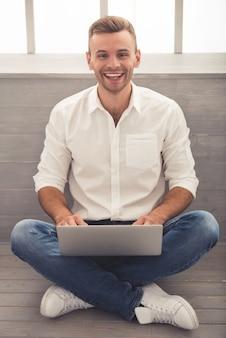 De zakenman in klassiek overhemd gebruikt laptop.