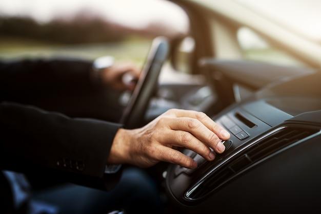 De zakenman in kostuum past een volume op zijn stereo-installatie aan terwijl het besturen van een auto.