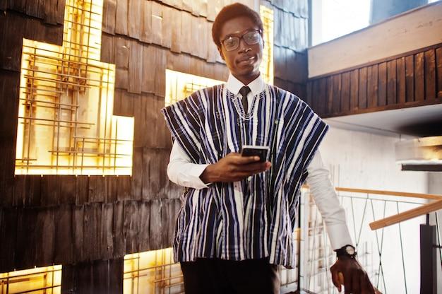 De zakenman in traditionele kleren en glazen met mobiele telefoon stelde dichtbij bij de moderne bouw binnen
