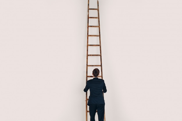 De zakenman in zwart kostuum heft de trede op. carrière en groei in bedrijfsconcept.