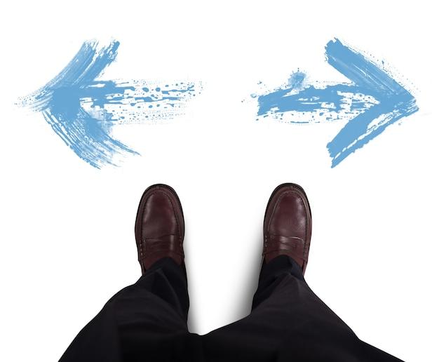 De zakenman kiest welke directionele witte pijl volgt