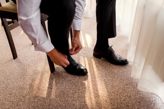 De zakenman kleedt schoenen, mens die klaar voor het werk, bruidegomochtend vóór huwelijksceremonie worden