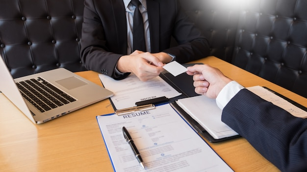 De zakenman luistert aan de jonge aantrekkelijke mens die over de antwoorden van het profielkandidaatgesprek verklaart