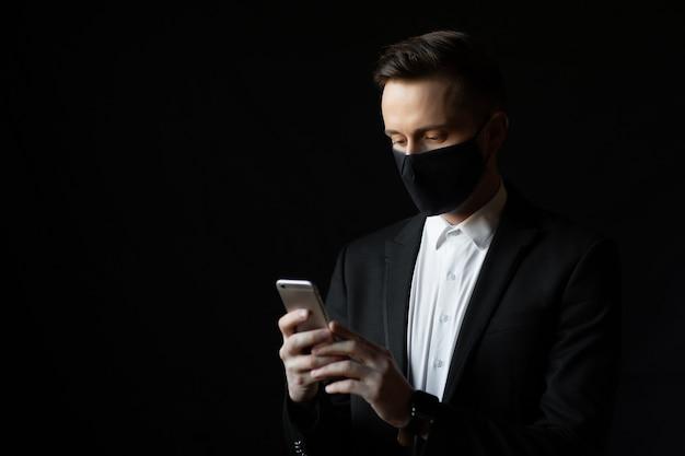 De zakenman met beschermend masker sms't, leest nieuws of werkt aan smartphone, geïsoleerd op zwarte achtergrond.