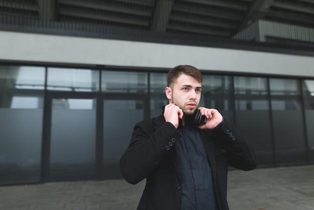 De zakenman met een baard en hoofdtelefoons op de hals stelt tegen muren van een modern gebouw.