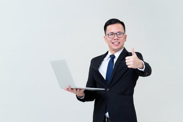 De zakenman met laptop computer het geven beduimelt omhoog