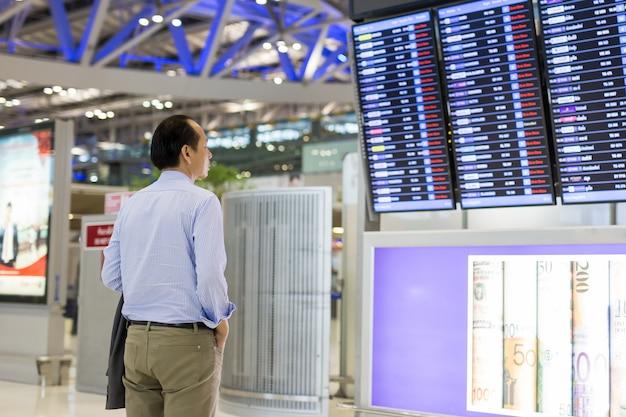 De zakenman met rugzak in luchthaven bekijkt vluchttijdschema.