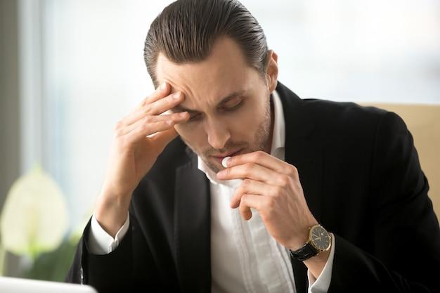 De zakenman neemt pil van hoofdpijn in bureau