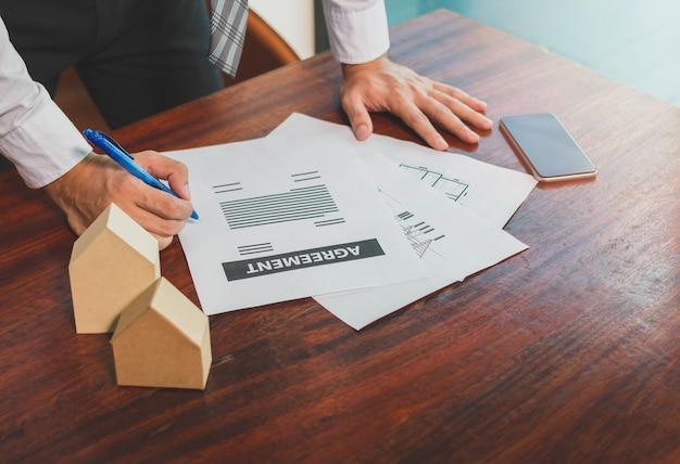 De zakenman ondertekent document overeenkomst - onroerende goederenconcept