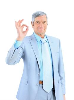 De zakenman op de leeftijd laat zien dat alles in orde is. geïsoleerd op een witte achtergrond.