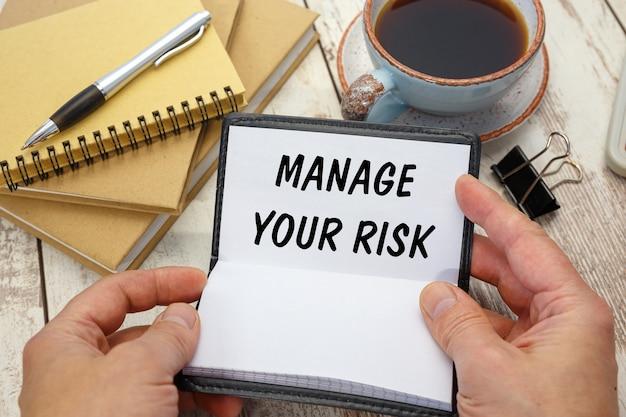 De zakenman opende een notitieboekje met het opschrift manage your risk