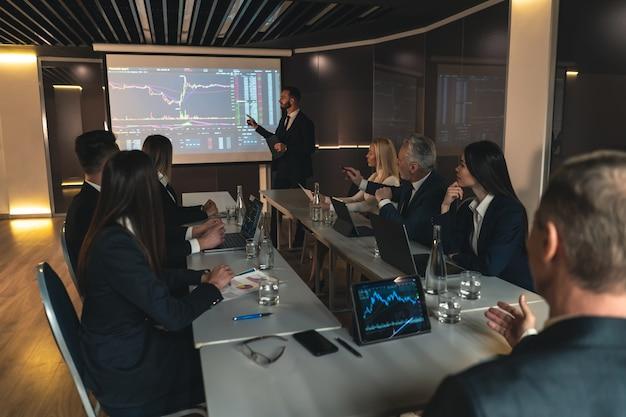 De zakenman presenteert zijn project op het scherm