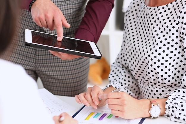 De zakenman richt een vinger op de tablet die het in zijn hand houdt