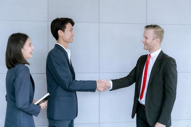 De zakenman schudt de handen akkoord gaat overeenkomst van het grote contract van de partijverkoop