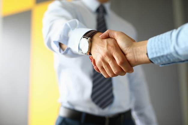 De zakenman schudt handen met vrouw in bureauclose-up.