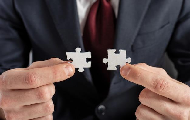 De zakenman sluit zich aan bij twee raadselstukken. concept van teamwork en partnerschap.