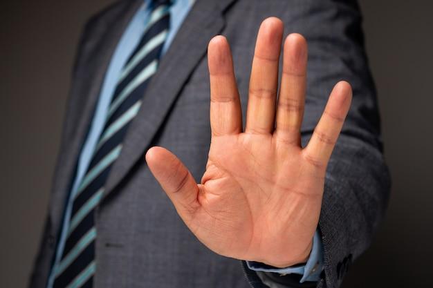De zakenman toont handteken voor einde en het houden, concept professionele waarschuwing voor einde nieuwe investering in wereldcrisis