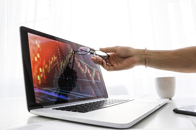 De zakenman toont het scherm op laptop de grafiek van de groei