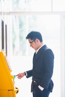 De zakenman trekt voor contant geld terug bij de atm-machine