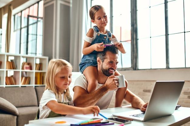De zakenman-vader probeert achter de laptop te werken wanneer zijn kleine dochters spelen, voor de gek houden en zich met hem bemoeien. freelance, thuiswerken.