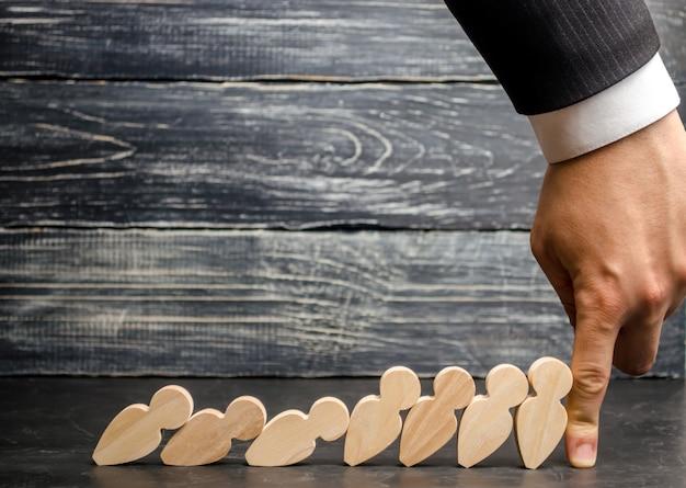 De zakenman van de leider houdt dalende domino's tegen. sterke en betrouwbare baas. moeilijkheden in zaken
