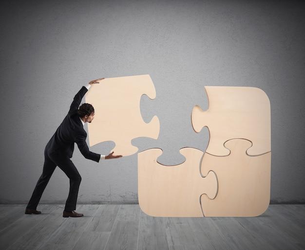 De zakenman voltooit een grote puzzel door een ontbrekend stuk in te voegen
