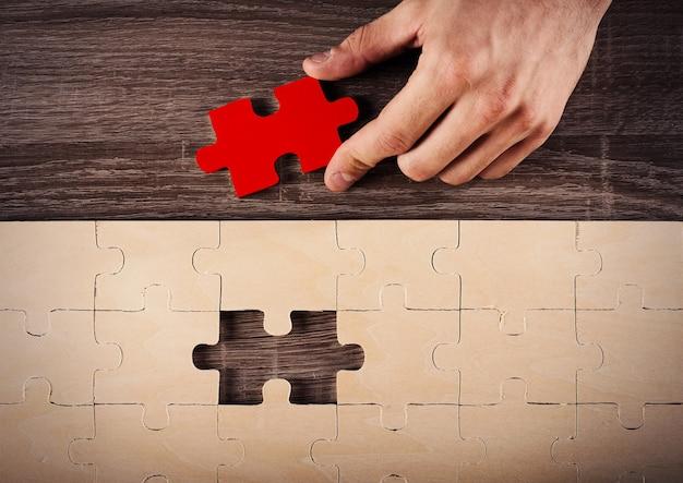 De zakenman voltooit een puzzel die het laatste stuk invoegt