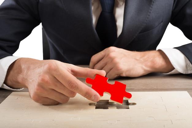 De zakenman voltooit een puzzel door een ontbrekend stuk in te voegen