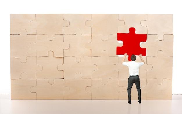 De zakenman voltooit een raadsel door een ontbrekend rood stuk in te voegen