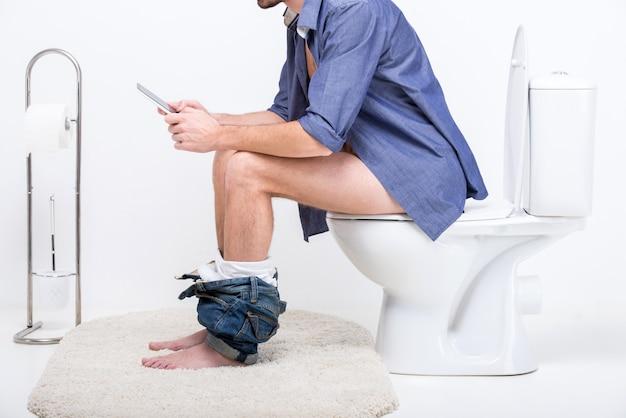 De zakenman werkt met tablet terwijl het zitten op toilet.