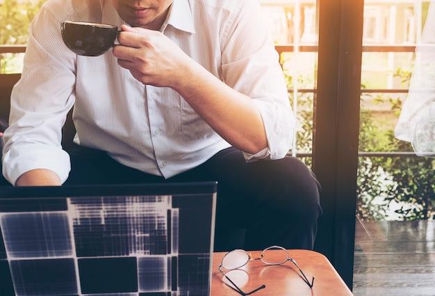 De zakenman werkt met zijn computer in koffiewinkel
