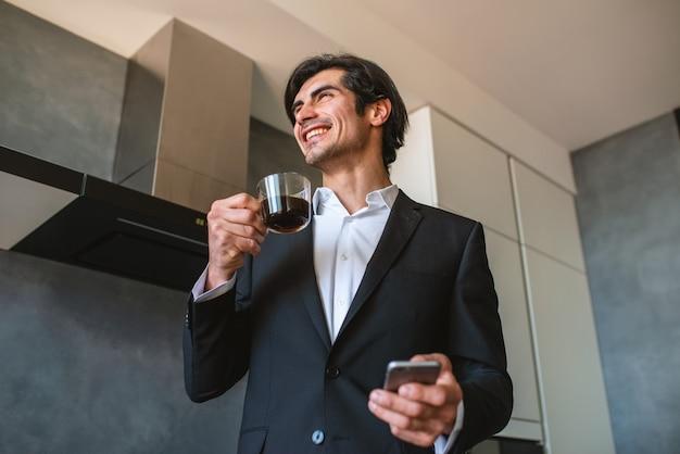 De zakenman werkt van ver bij huis met een smartphone wegens quarantaine van het coronavirus.