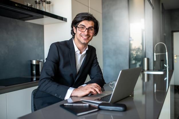 De zakenman werkt van ver bij huis met laptop wegens coronavirusquarantaine.