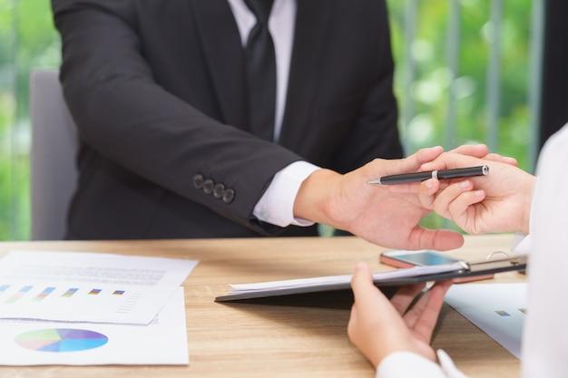 De zakenman zegt nr of houdt vast wanneer de vrouw pen voor het ondertekenen van een contract geeft