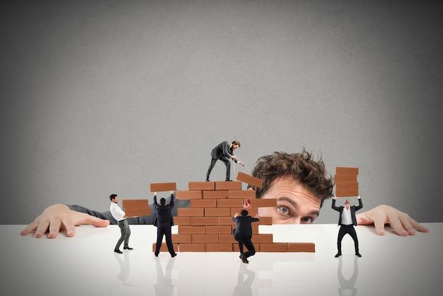 De zakenman ziet een teamwork van ondernemers samenwerken door een bakstenen muur te bouwen Premium Foto