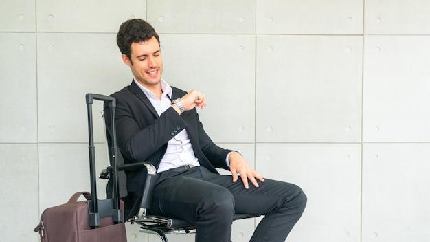 De zakenman zit op stoel wachtend met koffer en bekijkt horloge
