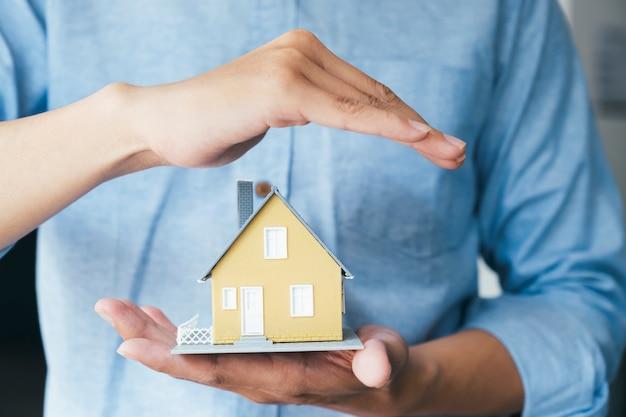 De zakenmanhand houdt het huis modelbesparing plattelandshuisje.