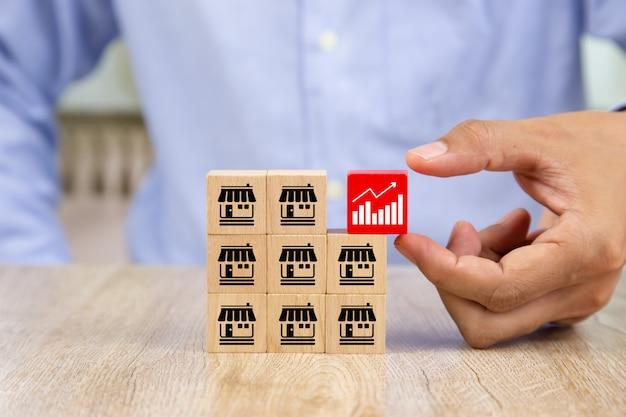 De zakenmanhand kiest houten blog met grafiekpictogram.