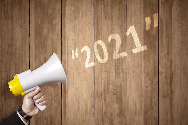 De zakenmanhand met een megafoon kondigt het gelukkige nieuwe jaar aan. gelukkig nieuwjaar 2021