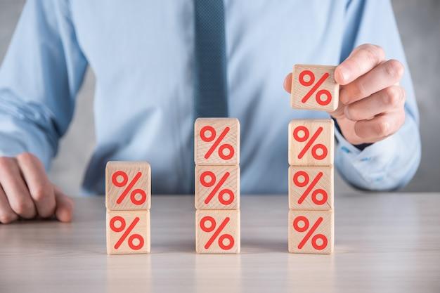 De zakenmanhand neemt een houten kubusblok dat het symboolpictogram van het percentage toont