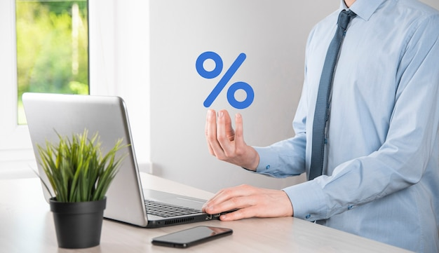 De zakenmanhand neemt een pictogram van het percentagesymbool. rente financiële en hypotheekrente concept.