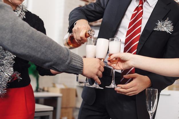 De zakenmanhanden schenken champagne in glazen aan zijn werknemerscel