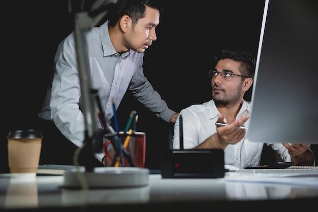 De zakenmanmedewerkers die van aasian werk bespreken bij nacht