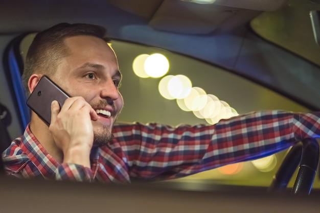 De zakenmantelefoon in de auto op de snelweg. avond nacht tijd