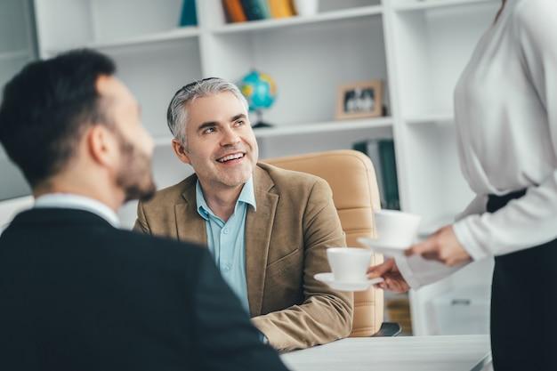 De zakenmensen die aan het bureau zitten