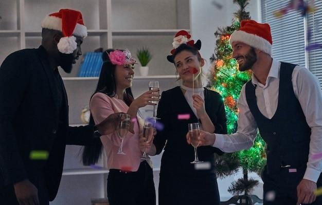 De zakenmensen die champagne drinken op de achtergrond van de kerstboom