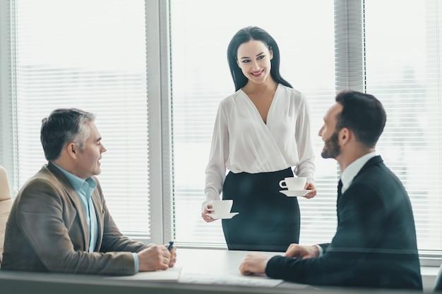 De zakenmensen zitten aan de kantoortafel