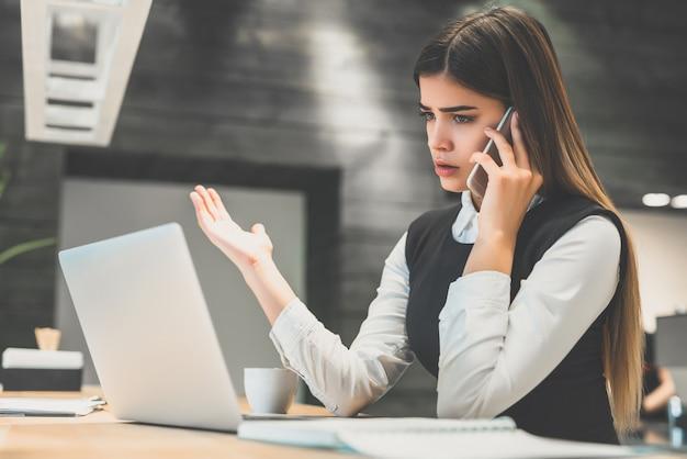 De zakenvrouw belt aan de desktop